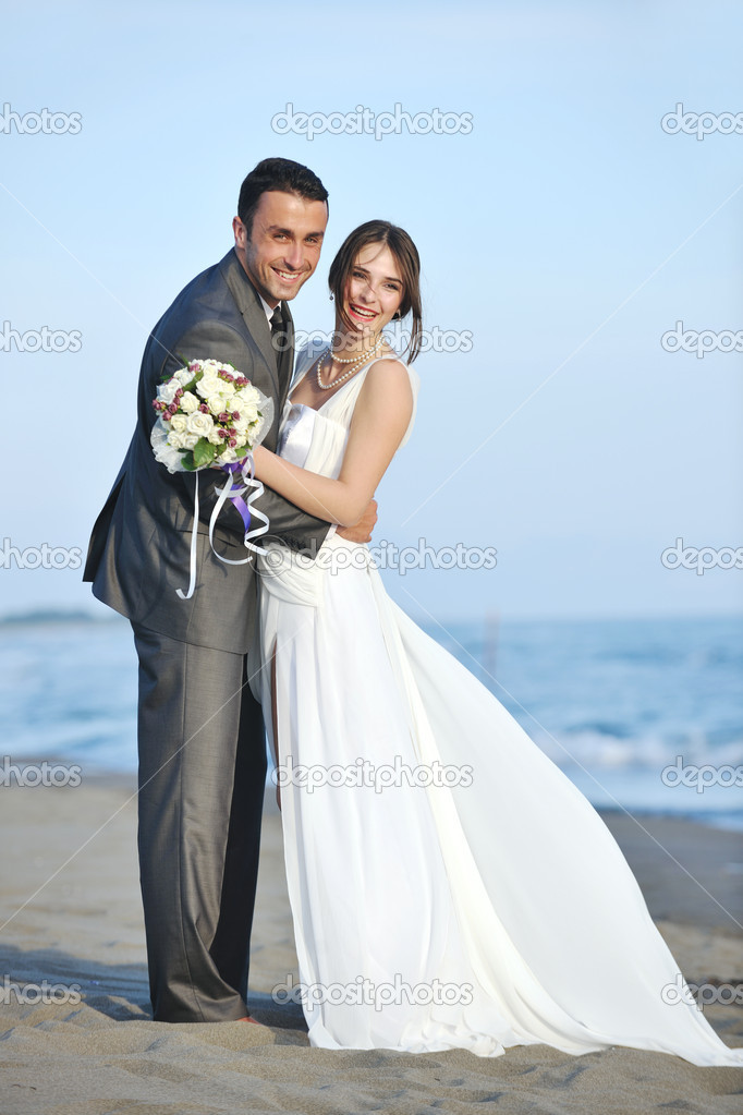 Happy just married young couple celebrating and have fun at beautiful beach sunset — Stock Photo #5844505