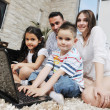 Happy young family have fun and working on laptop at home — Stock Photo #5858287