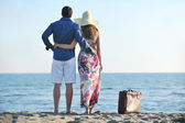 Couple on beach with travel bag — Stock Photo