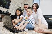 Feliz família jovem se divertir e trabalhando no laptop em casa — Fotografia Stock