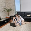 Happy young family have fun and working on laptop at home — Stock Photo #5863133
