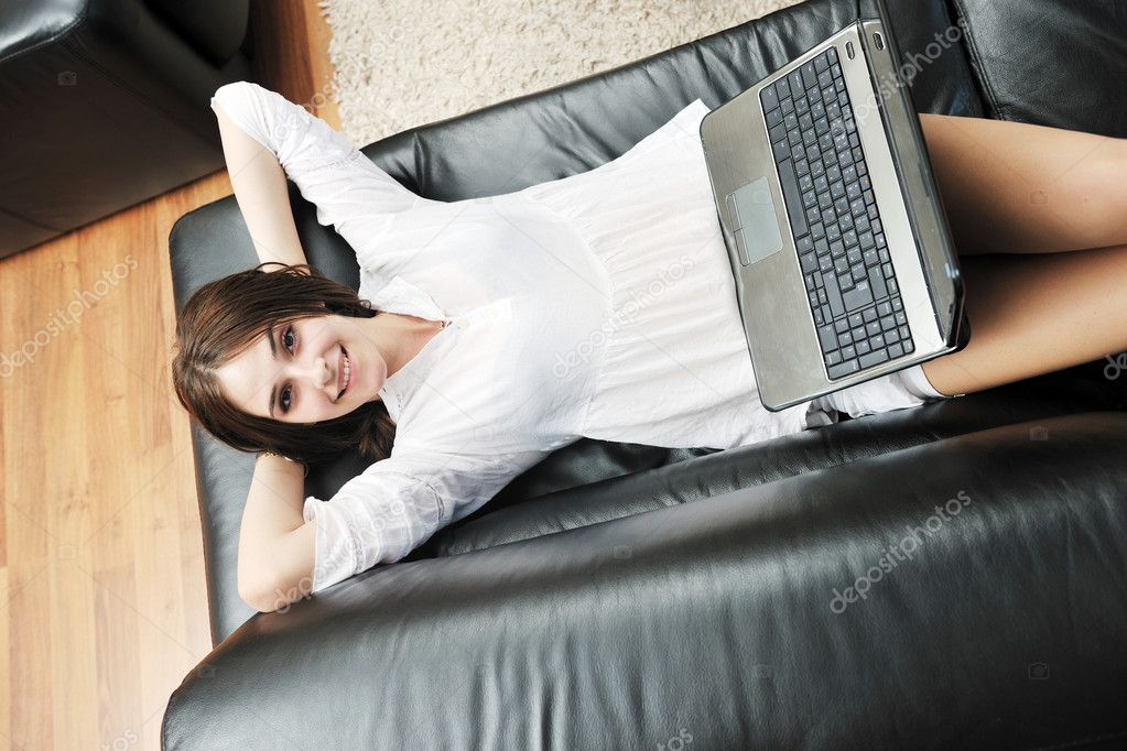 Happy young girl work on laptop computer  at modern  home livingroom indoor  Stock Photo #5863390