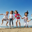 Happy child group playing  on beach - Stock Photo