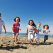 Happy child group playing  on beach — Foto Stock