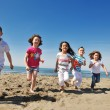Foto Stock: Happy child group playing on beach