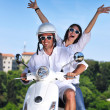 Portrait of happy young love couple on scooter enjoying summer t — 图库照片