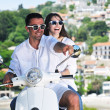 图库照片: Portrait of happy young love couple on scooter enjoying summer t