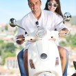 Photo: Portrait of happy young love couple on scooter enjoying summer t