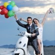 Just married couple on the beach ride white scooter — Stock Photo