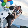 图库照片: Just married couple on the beach ride white scooter