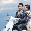 Just married couple on the beach ride white scooter — Stockfoto