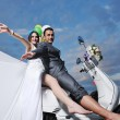 Стоковое фото: Just married couple on the beach ride white scooter