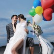 Just married couple on the beach ride white scooter — Stock Photo #6016126