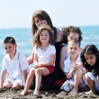 Group portrait of childrens with teacher on beach — Stock Photo