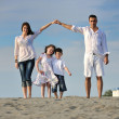 Family on beach showing home sign — Stock Photo #6017347