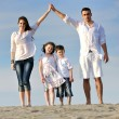 Family on beach showing home sign — Stock Photo #6017356