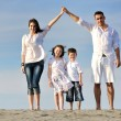 Family on beach showing home sign - Foto de Stock