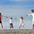 Family on beach showing home sign — Stock Photo #6017387