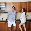 Happy young couple have fun in modern kitchen — Stock Photo