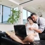 pareja alegre relajarse y trabaja en el ordenador portátil en casa moderna — Foto de Stock