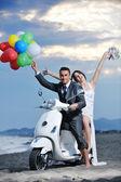 Просто семейная пара на скутере ездить белый пляж — Стоковое фото