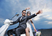 Just married couple on the beach ride white scooter — Photo