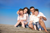 幸せな若い家族がビーチで楽しい時を過す — ストック写真