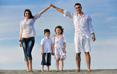Family on beach showing home sign — Stock Photo