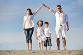 Familie am strand zeigt nach hause zeichen — Stockfoto