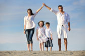 Family on beach showing home sign — Stockfoto
