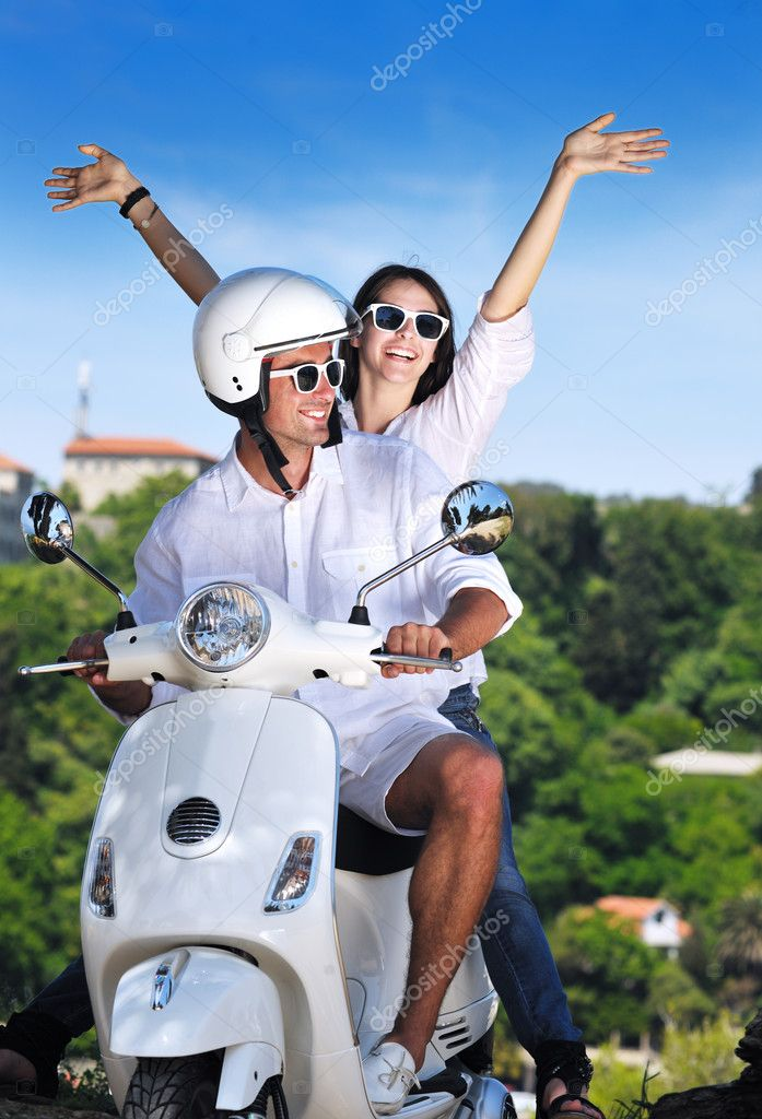Portrait of happy young love couple on scooter enjoying themselves in a park at summer time — Stock Photo #6011873