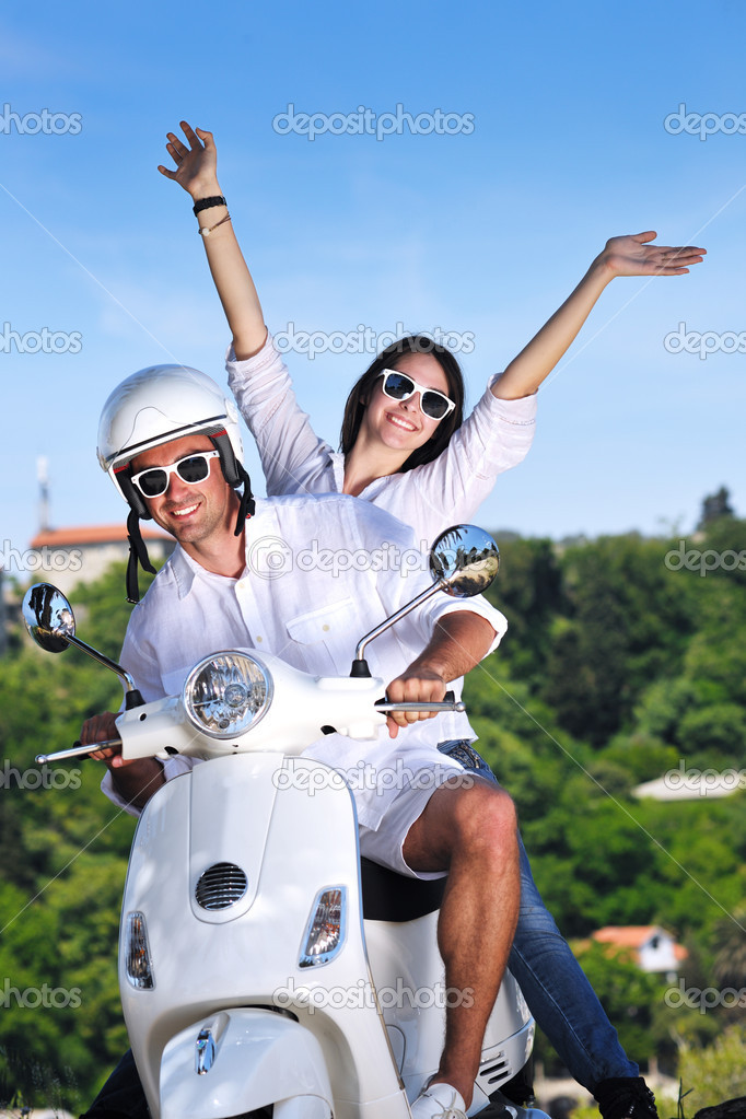 Portrait of happy young love couple on scooter enjoying themselves in a park at summer time — Stock Photo #6011983