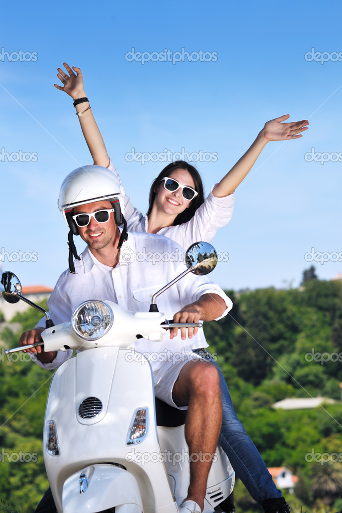 Portrait of happy young love couple on scooter enjoying themselves in a park at summer time  Stock Photo #6012022