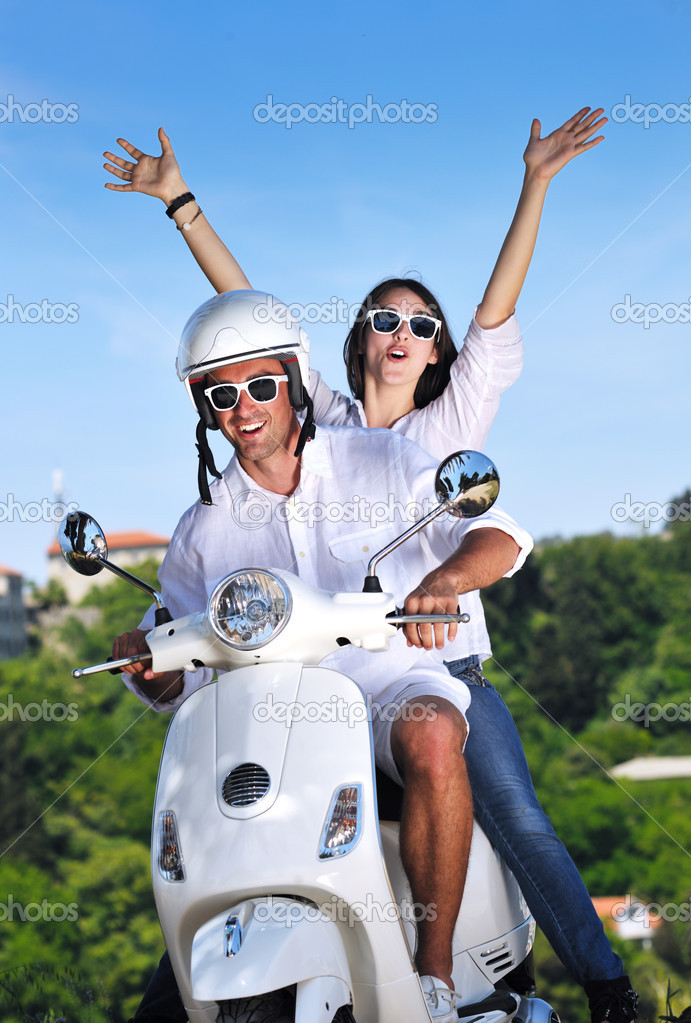 Portrait of happy young love couple on scooter enjoying themselves in a park at summer time — Stock Photo #6012052