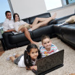 Happy young family have fun and working on laptop at home — Stock Photo #6020669