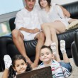 Happy young family have fun and working on laptop at home — Stock Photo