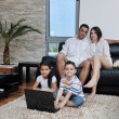 Happy young family have fun and working on laptop at home — Stock Photo #6020977