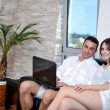 Joyful couple relax and work on laptop computer at modern home — Stock Photo #6020995