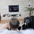 Family wathching flat tv at modern home indoor - Stockfoto