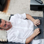 Portret van een ontspannen jonge kerel met behulp van laptop thuis — Stockfoto