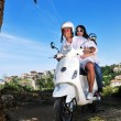 Portrait of happy young love couple on scooter enjoying summer t — Stockfoto