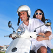 Portrait of happy young love couple on scooter enjoying summer t - Stock Photo