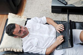 Portrait of a relaxed young guy using laptop at home — Foto de Stock