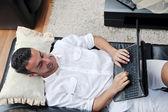 Retrato de un joven relajado mediante ordenador portátil en casa — Foto de Stock