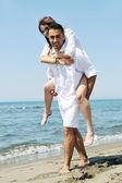 快乐的年轻夫妇在海滩上玩得开心 — 图库照片