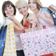 Happy young adult women  shopping with colored bags — ストック写真