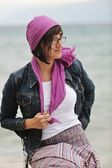 Beautiful young woman on beach with scarf — Stock Photo