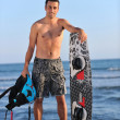 Stock Photo: Portrait of a young kitsurf man at beach on sunset