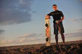 Porträt eines jungen kitsurf-mannes am strand bei sonnenuntergang — Stockfoto