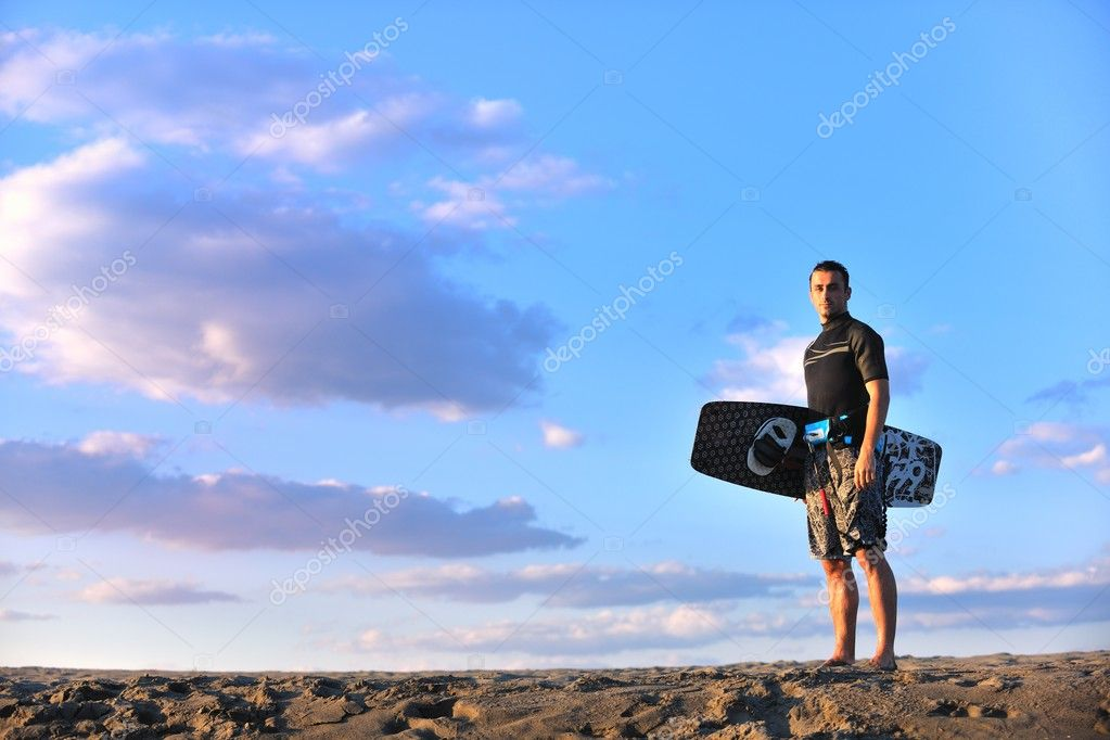 Portrait of a strong young  surf  man at beach on sunset in a contemplative mood with a surfboard  Stock Photo #6323172